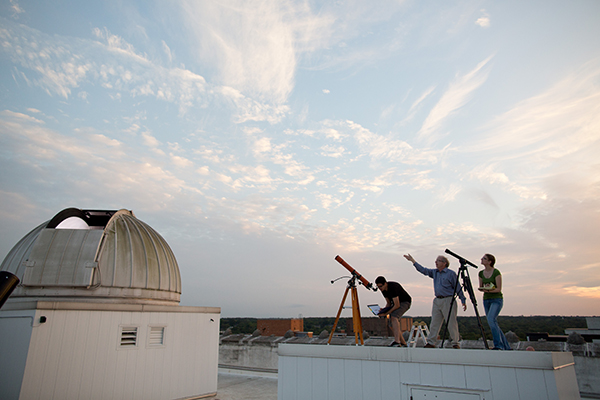 Three people on a roof top with telescopes observing the sky